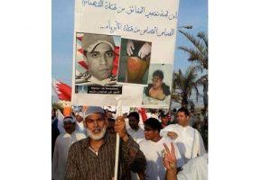 عبدالهادي مشيمع يحمل صورة ابنه الذي قتلته قوات الأمن